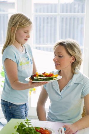 13 15 years: Girl serving plate of vegetables to woman