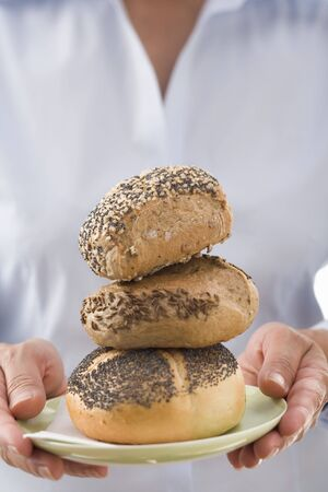 serve one person: Woman holding three bread rolls on a plate