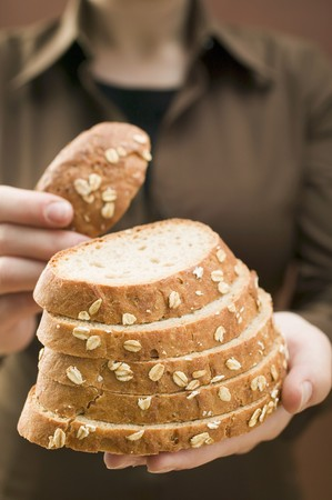 rolled oats: Woman holding slices of bread (with rolled oats) LANG_EVOIMAGES