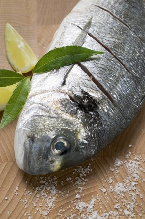 gilthead bream: Gilthead bream with salt, bay leaves and lemon wedges LANG_EVOIMAGES