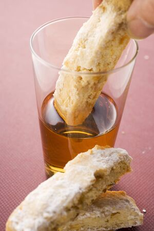 almond biscuit: Hand dipping cantucci (Italian almond biscuit) into glass of Vin Santo