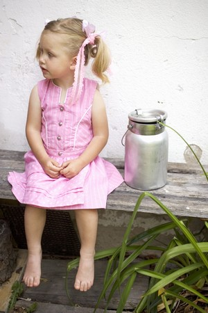 farmyards: Small girl on wooden bench beside milk can LANG_EVOIMAGES