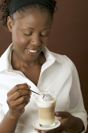 hot coffees: Woman holding a glass of latte macchiato