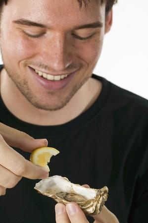 jus de citron: Man presser le jus de citron sur une hu�tre fra�che LANG_EVOIMAGES