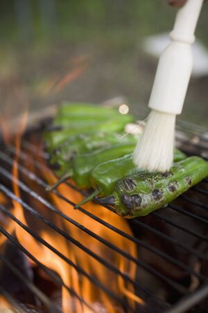 no movement: Green chillies on barbecue grill rack with brush