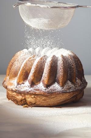 no movement: Sprinkling gugelhupf with icing sugar