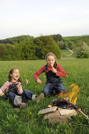 barbecues: Two girls grilling sausages over a camp-fire