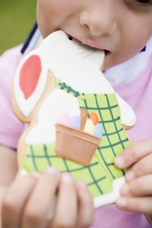 figurative: Child biting into Easter Bunny biscuit