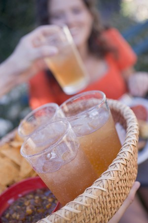 conviviality: Person serving a basket of iced tea and snacks