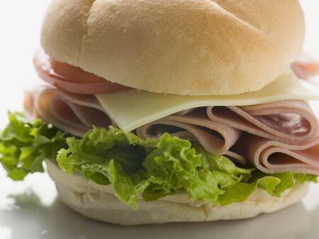 filled roll: Bread roll filled with ham, cheese, lettuce & tomato (close-up)