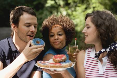 20 to 25 year olds: Young people with doughnuts & iced tea on the 4th of July (USA) LANG_EVOIMAGES