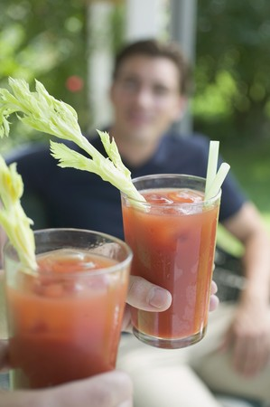 Hands holding two tomato drinks, young man in background