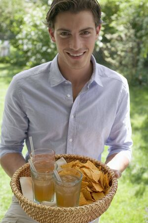 20 to 25 year olds: Man holding basket of drinks and tortilla chips LANG_EVOIMAGES