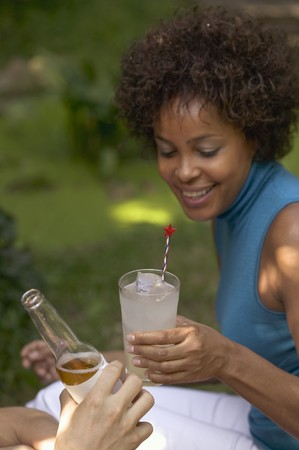 soda pops: Woman with a glass of lemonade at a garden party LANG_EVOIMAGES