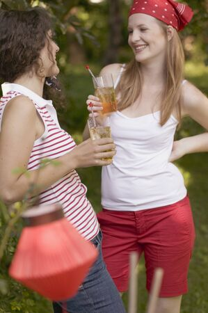 18 25 year old: Two young women drinking iced tea on the 4th of July (USA) LANG_EVOIMAGES