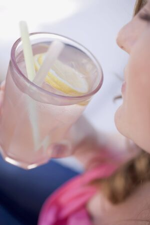 soda pops: Woman holding a glass of lemonade with straws LANG_EVOIMAGES