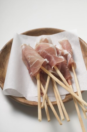 breadstick: Grissini wrapped in raw ham on wooden plate