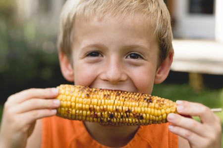 zea: Small boy eating grilled corn on the cob LANG_EVOIMAGES