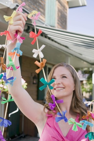 festoons: Woman with coloured garlands for garden party