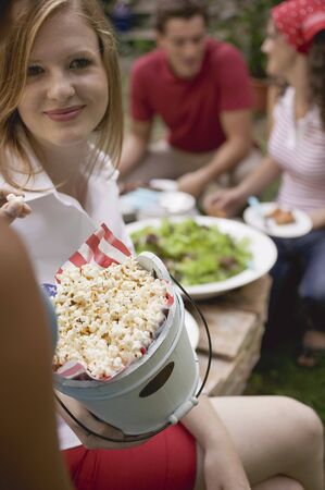 Young people with popcorn and salad at a garden party