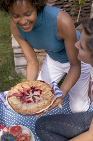 blueberry pie: Mujer sirviendo tarta de ar�ndanos en un d�a de campo el 4 de julio (EE.UU.)