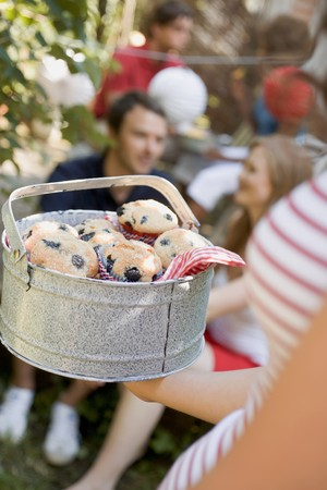 four year olds: Woman holding a tin of blueberry muffins at a garden party