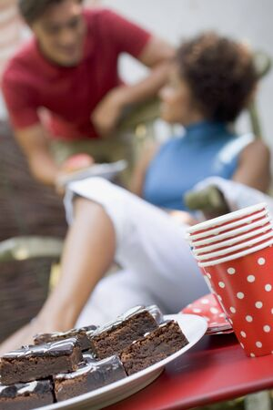 20 to 25 year olds: Brownies at garden party for 4th of July, couple in background
