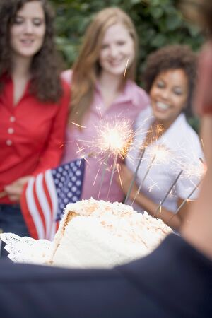 sociable: Man serving coconut cake with sparklers (4th of July, USA)