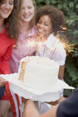 four year olds: Man serving coconut cake with sparklers (4th of July, USA)