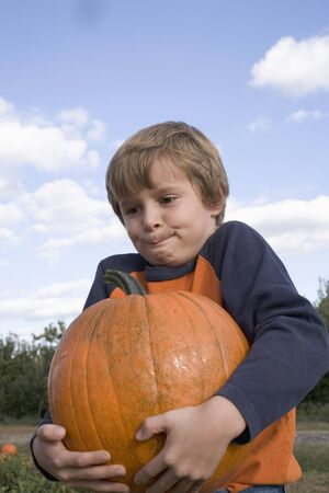 10 to 12 year olds: Boy holding a large pumpkin in a field LANG_EVOIMAGES