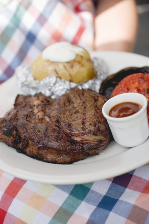 barbecues: Woman holding plate of grilled steak and accompaniments LANG_EVOIMAGES