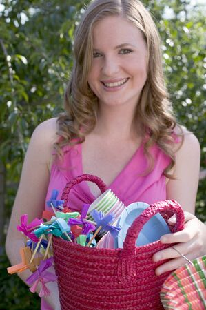 20 to 25 year olds: Woman holding basket of decorations for a garden party