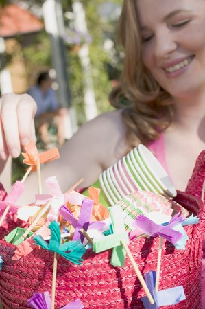 festoons: Woman holding basket of decorations for a garden party