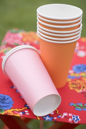 barbecues: Coloured paper cups on folding stool in garden