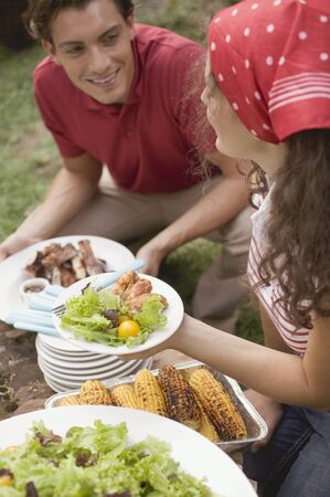 Young couple at a barbecue LANG_EVOIMAGES