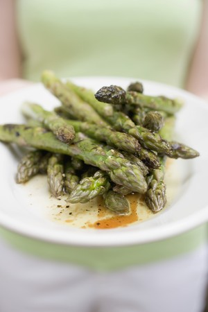 food: Woman holding a plate of grilled green asparagus
