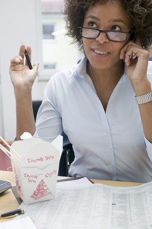 asian noodle: Woman in office with Asian noodle dish, on the phone