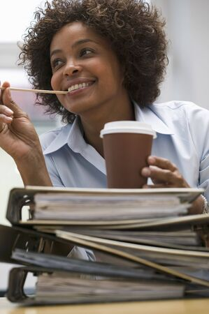 coffee breaks: Woman in office with cup of coffee on pile of files