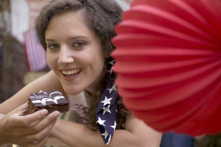 4th of july: Woman eating a brownie on the 4th July (USA)