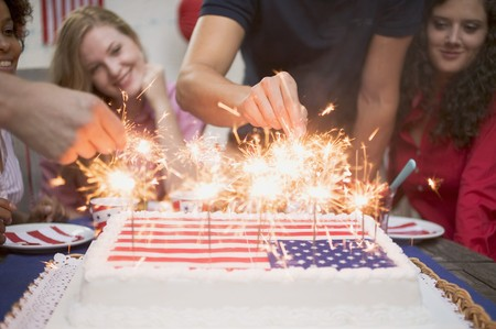 Hands lighting sparklers on a cake (4th of July, USA)