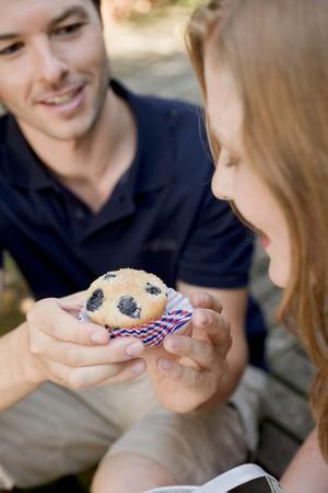 blueberry muffin: Man handing woman a blueberry muffin