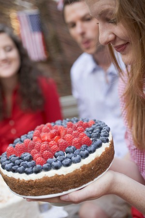 Woman holding a berry cake (4th of July, USA)