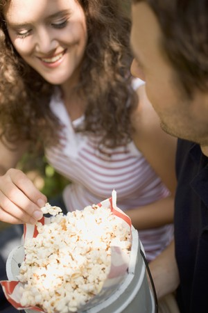 20 to 25 year olds: Couple eating popcorn at a picnic LANG_EVOIMAGES