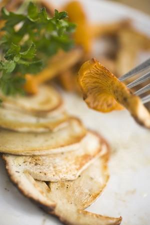 cep: Fried chanterelle on fork above sliced cep LANG_EVOIMAGES