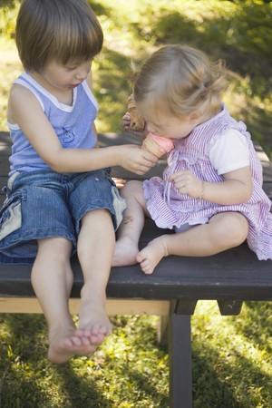 eating area: Two children with ice cream cones on garden table