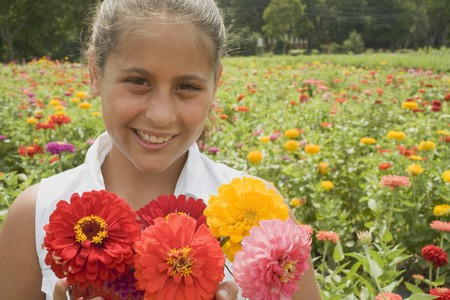 16 to 17 year olds: Girl with summer flowers in front of a field of flowers