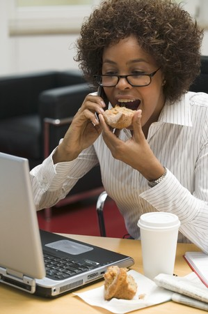25 to 30 year olds: Woman eating muffin while working on computer