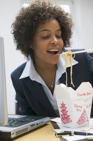 asian noodle: Woman in office eating Asian noodle dish