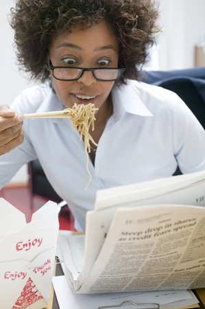 asian noodle: Woman in office eating Asian noodle dish & reading newspaper LANG_EVOIMAGES