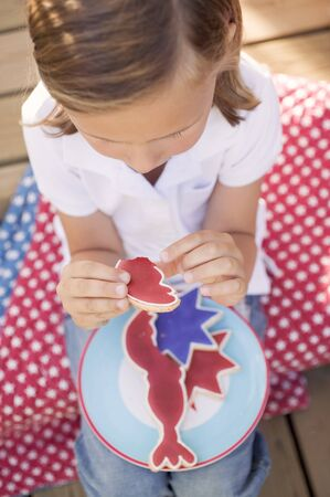 figurative: Small girl with a partly-eaten cookie (4th of July, USA)